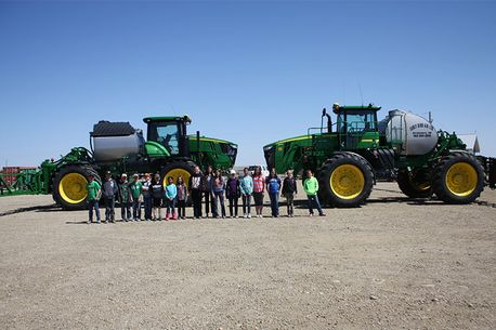 Group standing by tractors